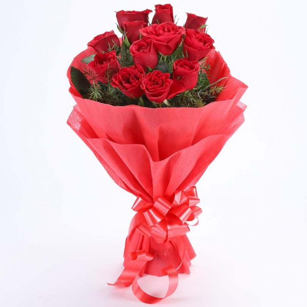 10 red roses with small green leaves wrapped in red paper and tied with red ribbon